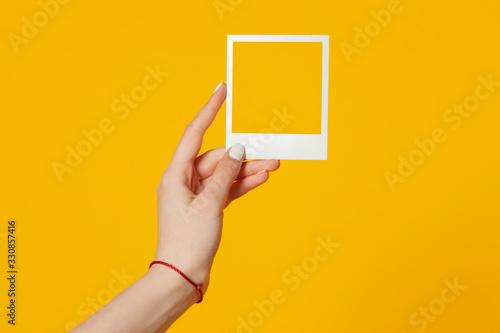 Fototapeta female hand holds empty instant photo frame isolated on yellow background obraz