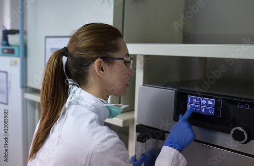 Biologist working on display of incubator in laboratory Canvas Print