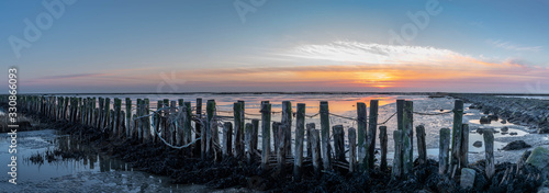 An impressive panorama view of the dike foreland near the imposing Eider barrage, Sunset over the the Wadden Sea, mudflat, tideland on the Northsea Wesselburenerkoog