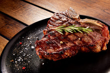 Grilled Beef Steak With Rosemary, Salt And Pepper On Black Stone Plate. Grilled Striploin Sliced Steak. Juicy Thick Grilled Beef Steak Seasoned With Rosemary Fresh Of The Summer BBQ.