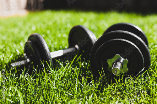 obraz PCV keeping fit and exercising outdoor, set of heavy dumbbells on green grass lawn in a backyard under direct sunlight