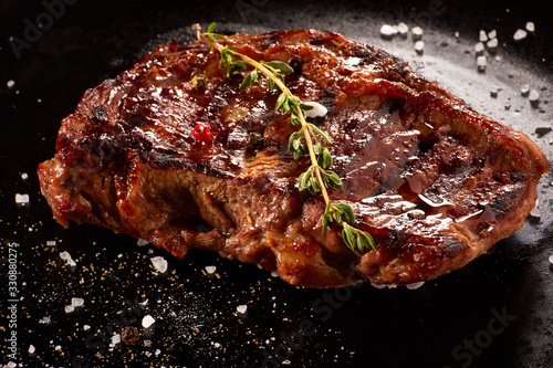 Fototapeta Grilled beef steak with rosemary, salt and pepper on black stone plate. Grilled striploin sliced steak. Juicy thick grilled beef steak seasoned with rosemary fresh of the summer BBQ. obraz