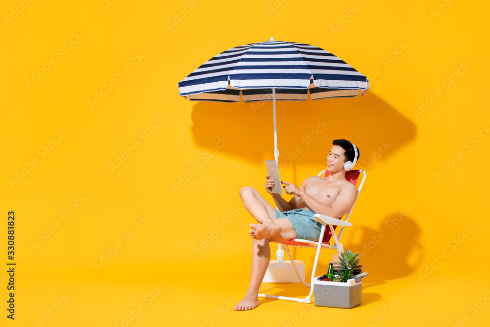 Fototapeta Portrait of young shirtless Asian man sitting on beach chair relaxing and listening to music in isolated summer yellow background