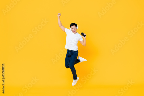 Obraz Happy young Asian man wearing headphone listening to music from mobile phone and jumping with fist raising isolated on yellow background - fototapety do salonu