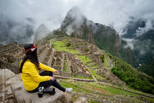 Obraz Young Asian woman traveler looking at Machu Picchu, one of seven wonders and famous tourist attraction in Cusco Region of Peru. This majestic place has known as 'Lost City of the Incas' - fototapety do salonu