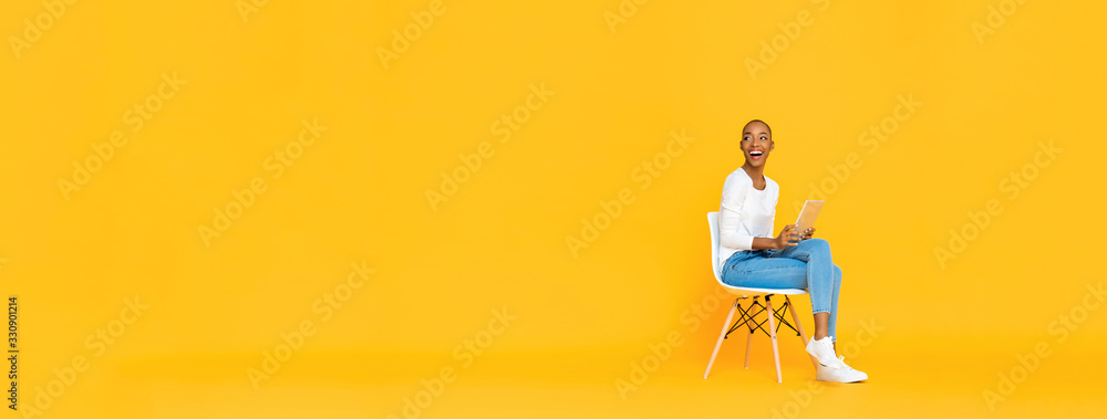 Fototapeta Trendy smiling African American woman sitting on a chair using tablet computer thinking and looking at empty space aside isolated yellow banner background
