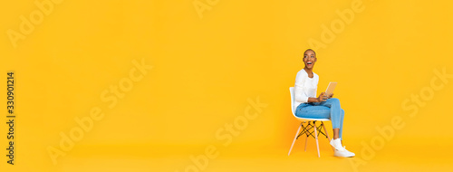 Fototapeta Trendy smiling African American woman sitting on a chair using tablet computer thinking and looking at empty space aside isolated yellow banner background obraz