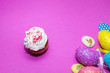 Leinwanddruck Bild - on a pink background close-up of colored Easter eggs and cupcake, holiday background