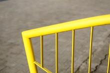 Closeup Shot Of Yellow Metal Railings On The Sidewalk