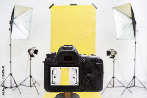 Camera in a photo studio with yellow backdrop and light equipment Fototapet