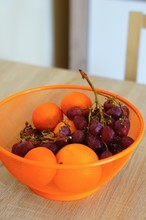Orange Bowl Of Grapes And Oranges On A Wooden Table