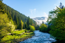 Mountain River On A Misty Sunrise. Stunning Nature Scenery With Fog Rolling Above The Trees In Fresh Green Foliage On The Shore In The Distance. Beautiful Countryside In Morning Light