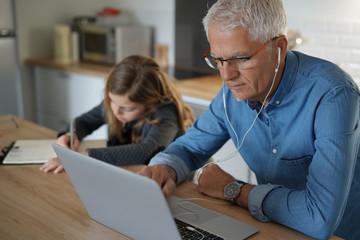 Fototapeta na wymiar Father and school-girl working form home, telework and e-learning