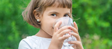 Child Drinks Water From A Glas...