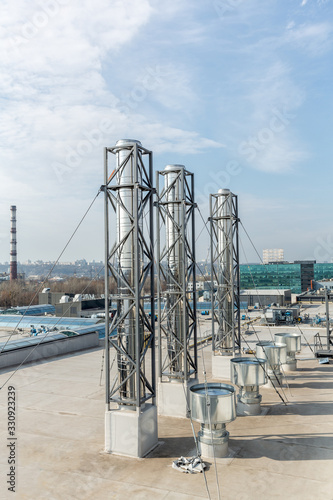 Photo stainless steel chimneys and baffles on the roof of the building