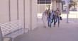 4 girls talking and laughing and walking around an urban city corner
