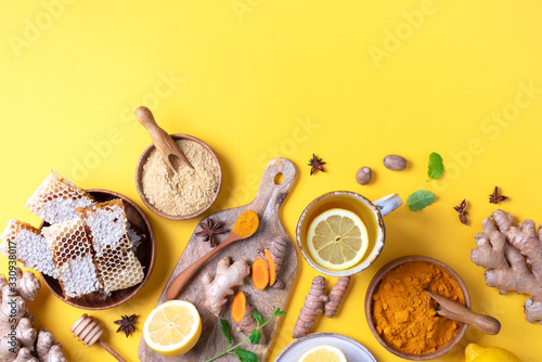 Photo Organic ingredients for turmeric hot tea on yellow background