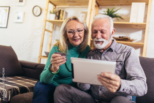 Happy seniors ordering dinner online on laptop, paying with credit card at home Wallpaper Mural