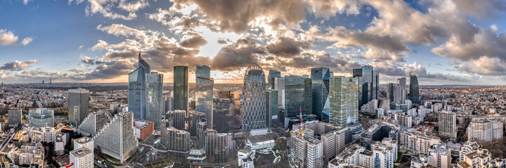Aerial panoramic drone shot of La defense skyscraper in Paris with clouds and sunset