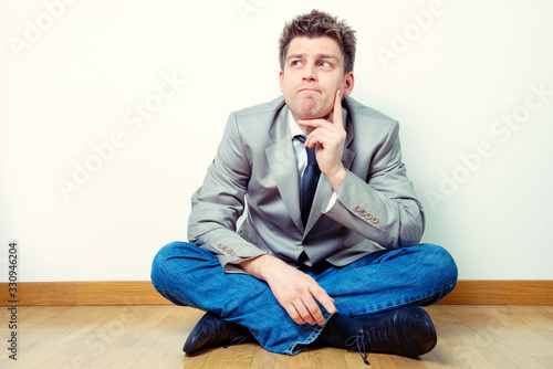 Portrait of a man sitting in interrogative expression Fototapeta