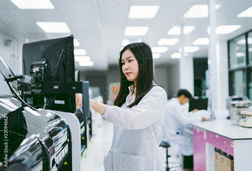 young female scientist working with automation blood analyzer in medical laborat Wallpaper Mural