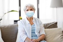 Health, Safety And Pandemic Concept - Senior Woman Wearing Protective Medical Mask For Protection From Virus At Home