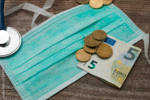Cuadros en Lienzo Medical face mask on a wooden table with euro coins and a five euro banknote on top of it