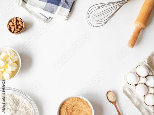Fotografering Frame of various baking ingredients - flour, eggs, sugar, butter, dry yeast, nuts and kitchen utensils on white background