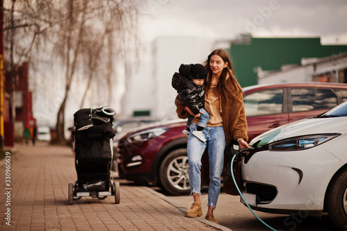 Young mother with child charging electro car at the electric gas station фототапет