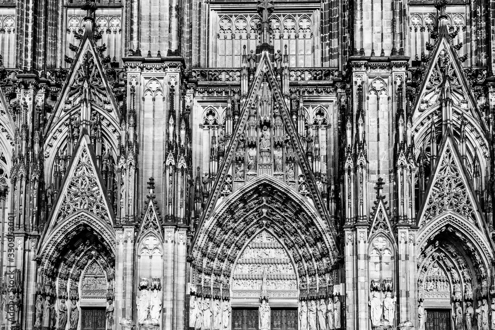 Fototapeta Sculptures and carvings on the facade of the gothic cathedral a UNESCO world heritage site in Cologne, Germany in black and white
