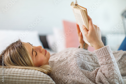 Young woman lies on her back in bed reading a book