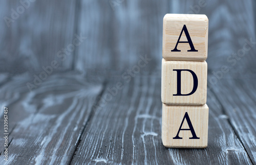 Photo concept of the word ADA on cubes on a wooden gray background