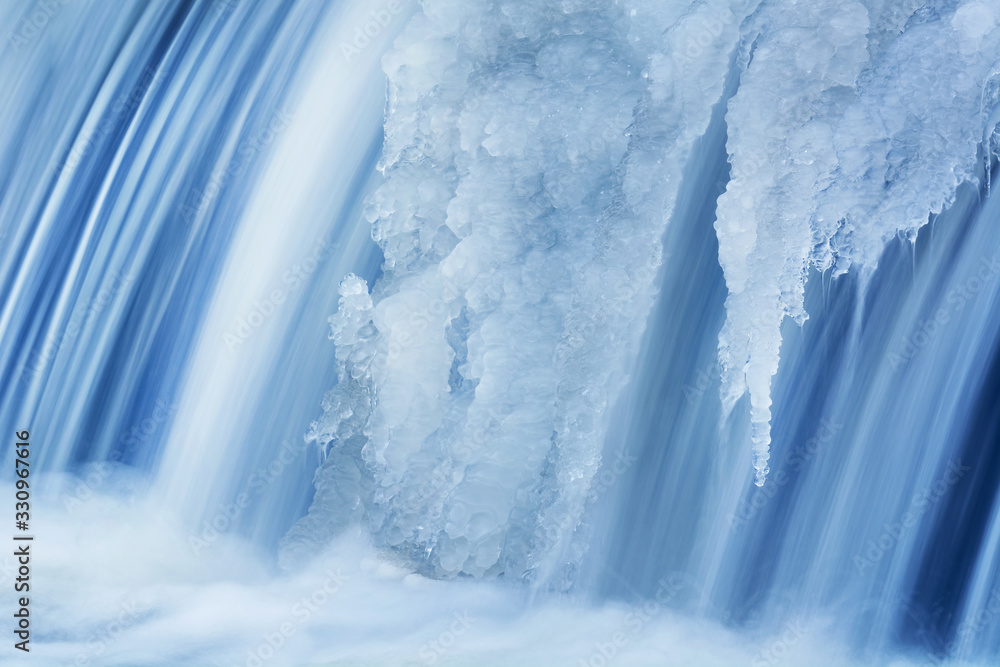 Fototapeta Winter, Portage Creek Cascade captured with motion blur and framed by ice, Milham Park, Kalamazoo, Michigan, USA