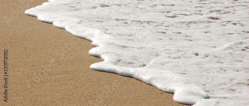 Cuadros en Lienzo Bannière d'une douce vague blanche pleine d'écume sur le sable d'une plage de sa