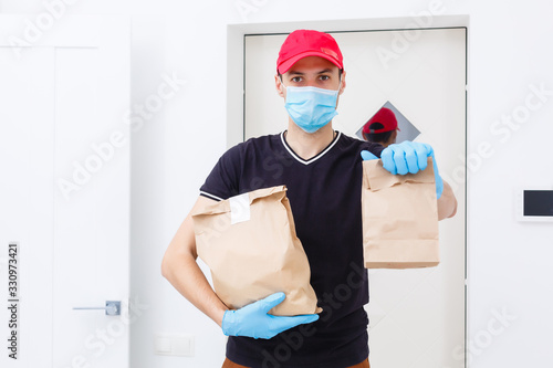 Obraz Delivery man holding paper bag with food on white background, food delivery man in protective mask - fototapety do salonu