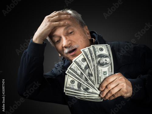 Photo Senior gentleman holding a stack of money