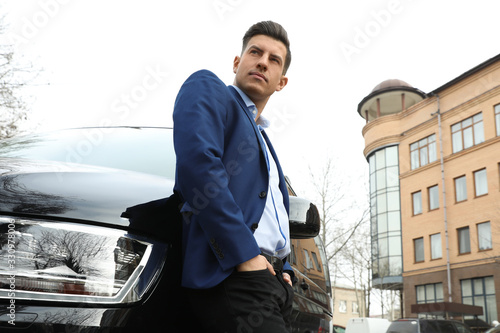 Photo Handsome man near modern car outdoors, low angle view