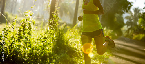 Obraz Young fitness woman running at morning tropical forest trail - fototapety do salonu