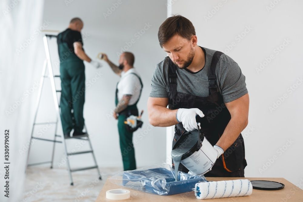 Fototapeta Efficient renovation crew painting white walls of new build home