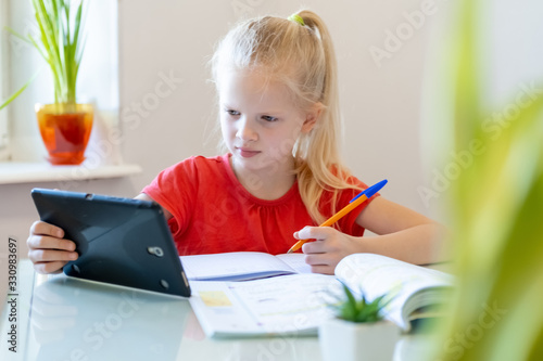Obraz Distance learning online education. Schoolgirl studying at home with digital tablet and doing school homework. Training books and notebooks on table - fototapety do salonu