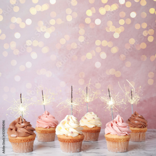 fototapeta na drzwi i meble Birthday cupcakes with sparklers on table against light pink background