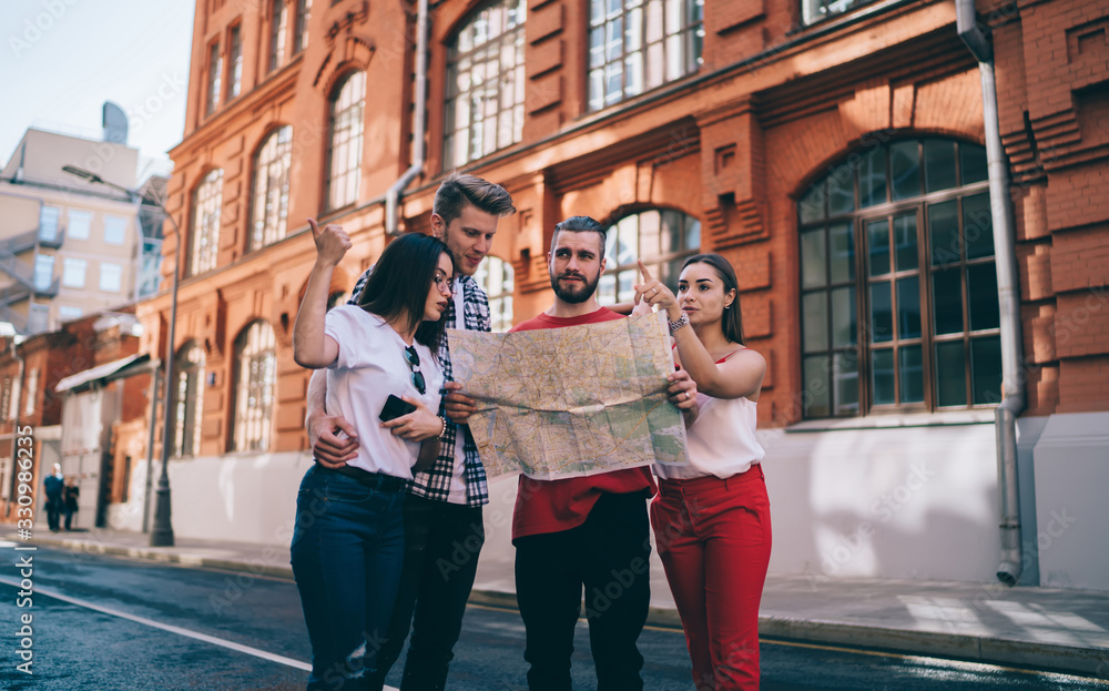 Fototapeta Calm adult lost travelers with paper map asking for advice locals on street in city