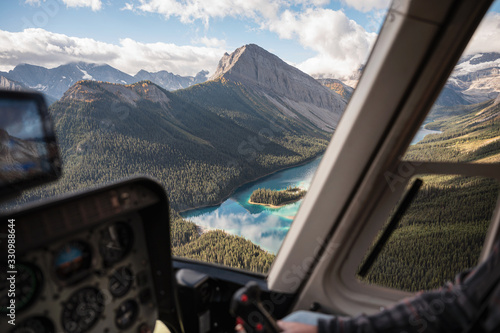 Inside of helicopter flying on rocky mountains with colorful lake Canvas-taulu