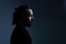 Studio Dramatic Profile Portrait Of A Young Bearded Guy Of Thirty Years Old, With Long Hair Gathered, Looks Down. On A Dark Background. A Ray Of Light On The Face. Dramatic Light