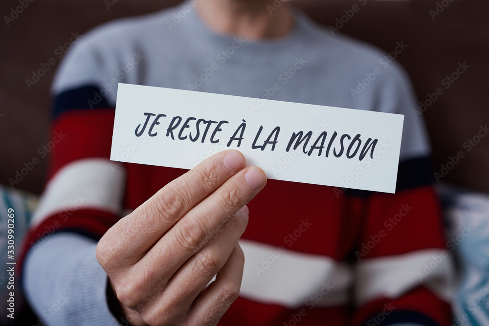 Fototapeta man showing the message I stay at home in french