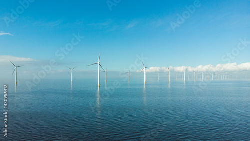 Obraz Windmill row of windmills in the ocean by the lake Ijsselmeer Netherlands, renewable energy windmill farm Flevoland - fototapety do salonu