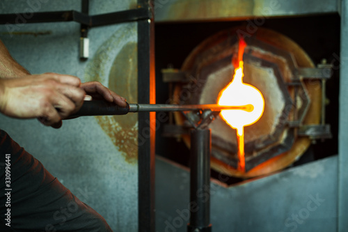 A close up selective focus view of a glassblower inserting a blowpipe into a burning furnace, glass maker glory hole, with copy space to right Wallpaper Mural