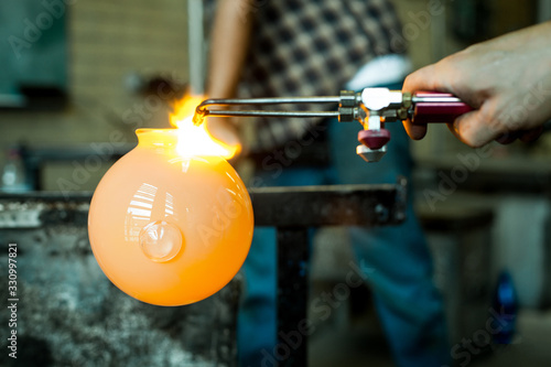 Photo A close up selective focus view on the hands of a glassblower at work with a molten glob of glass on the end of a blowpipe, shaping a bowl with copy space