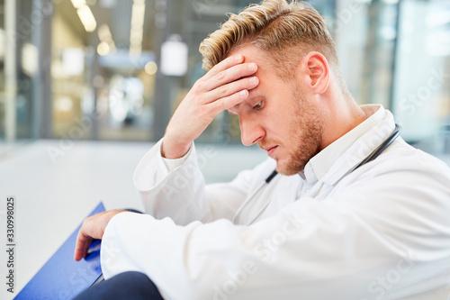 Canvastavla Junger Mann als Arzt mit der Hand an der Stirn