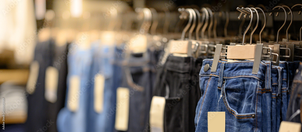 Fototapeta Jeans or Denim pants (trousers) hanging on rack in clothes shop. Fashion product collection in clothing store for selling. Textile industry and business concept
